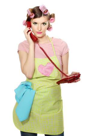 beautiful young housewife with red telephone isolated on white photo