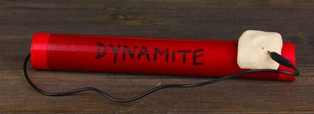 detonating: Dynamite on wooden table on grey background