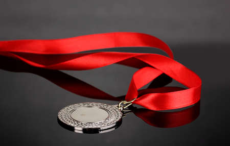 Silver medal on grey background Stock Photo - 13870757