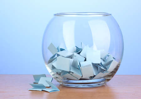 Pieces of paper for lottery in vase on wooden table on blue background Stock Photo - 13870736