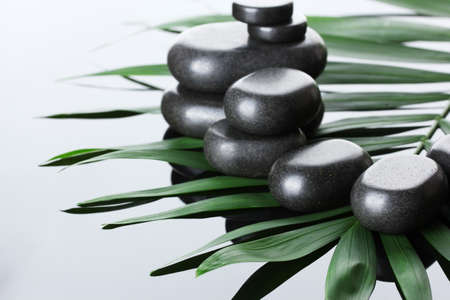 Spa stones on green palm leaf on grey background photo