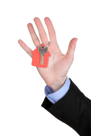 concluding: Key with house-shaped charm in hand isolated on white Stock Photo