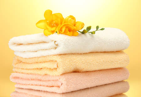 colorful towels and flowers on yellow background photo