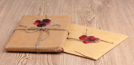 Parcel and envelope with sealing wax on wooden background photo