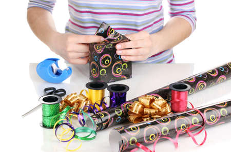 Wrapping presents surrounded by  paper, ribbon and bows photo