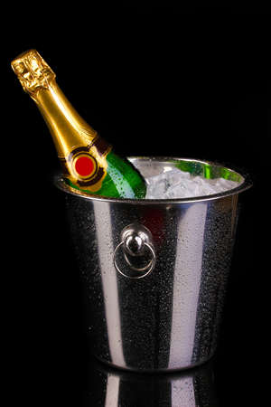 Bottle of champagne in bucket isolated on black Stock Photo - 13874576