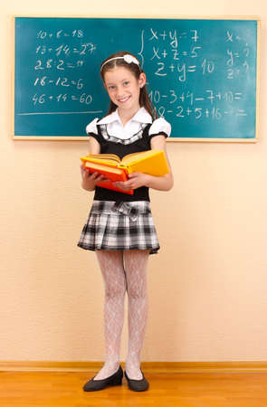Girl School: beautiful little girl in school uniform with books in class room Stock Photo