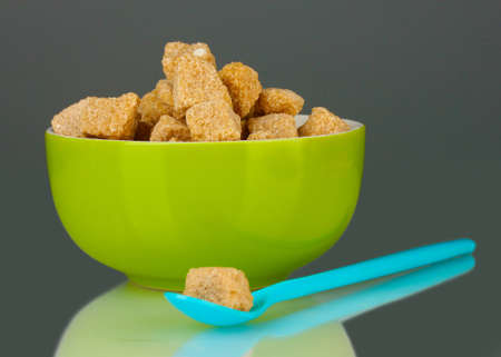 Colorful bowl with brown cane sugar cubes with colorful spoon on grey background close-up photo