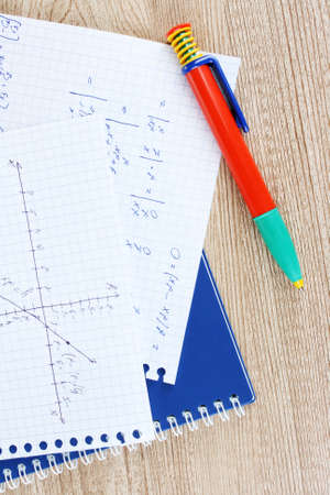 Math, physics and geometry on copybook page on a wooden table photo