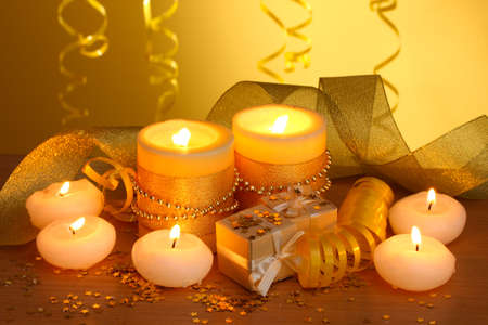 Beautiful candles, gifts and decor on wooden table on yellow background Stock Photo - 13904790