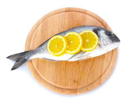 Fresh fish with lemon on wooden cutting board isolated on white  photo