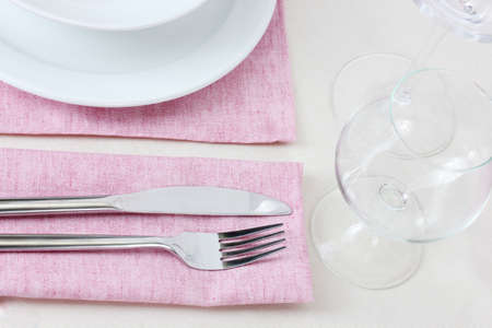 Table setting with fork, knife, plates and napkin photo