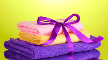 Colorful towels with ribbon on green background Stock Photo - 13904794