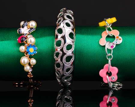 Three fashion bracelets on the green cloth on black background Stock Photo - 13904954