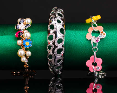 Three fashion bracelets on the green cloth on black background Stock Photo - 13904954