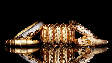 Beautiful golden bracelets isolated on black background photo