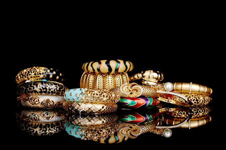 fashion jewelry: Beautiful golden bracelets isolated on black background Stock Photo