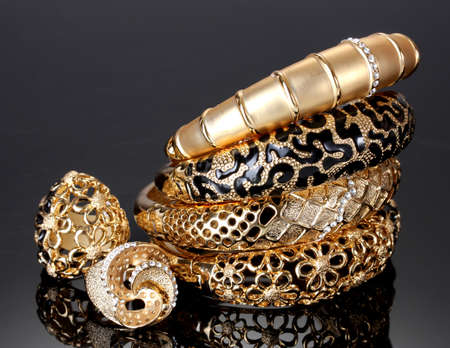 Beautiful golden bracelets and rings on grey background Stock Photo - 13904928
