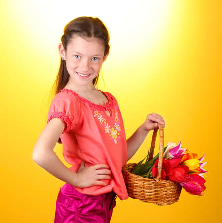 resent: Portrait of beautiful little girl with tulips in basket  on yellow background