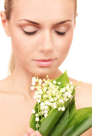 Beautiful young woman with a bouquet of lilies of the valley on white background close-up photo
