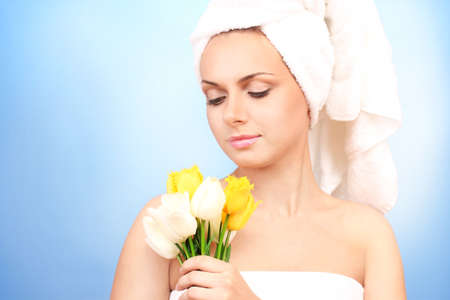 Beautiful young woman after shower with a towel on her head and with a bouquet of tulips on blue background close-up photo