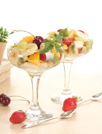 Fresh fruits salad and strawberries on wooden table photo