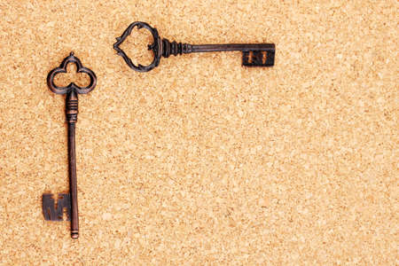 Two antique keys on cork background Stock Photo - 13950347