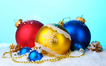 beautiful bright Christmas balls and cones in snow on blue background