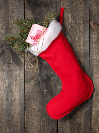 Christmas sock with gifts on wooden background