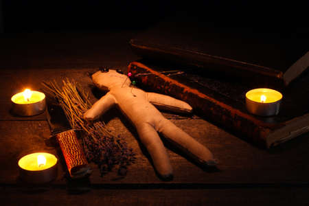 Voodoo doll boy on a wooden table in the candlelight