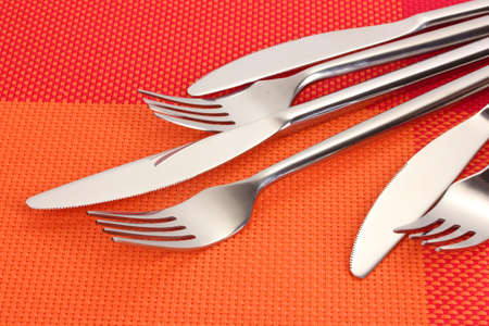 Forks and knives on a red tablecloth