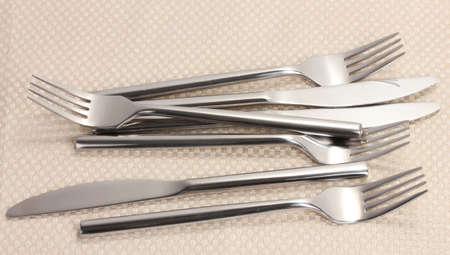 Forks and knives on a beige tablecloth