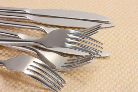 Forks and knives on a beige tablecloth closeup Stock Photo - 14135146