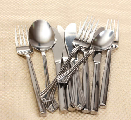 Forks, spoons and knives on a beige tablecloth