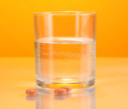 Glass of water and pills on orange background