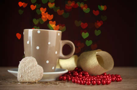 cup of coffee on wooden table on bright bokeh backdground