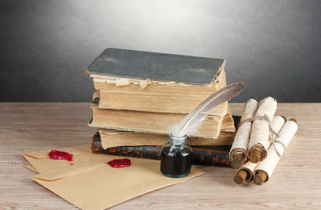 old books, scrolls, feather pen and inkwell on wooden table on grey background Stock Photo - 14135131