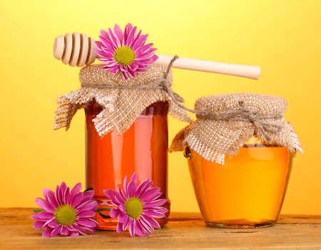 Sweet honey in jars with drizzler on wooden table on yellow background