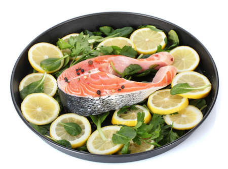 Red fish with lemon, parsley and pepper on plate isolated on white