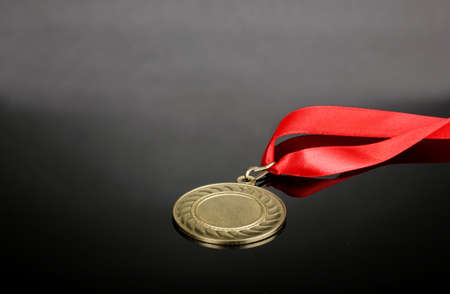 Gold medal on grey background Stock Photo - 14135059