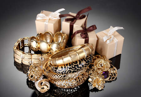 Beautiful golden jewelry and gifts on grey background Stock Photo - 14135147