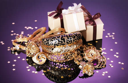 Beautiful golden jewelry and gifts on purple background