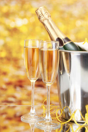 Champagne bottle in bucket with ice and glasses of champagne, on yellow background