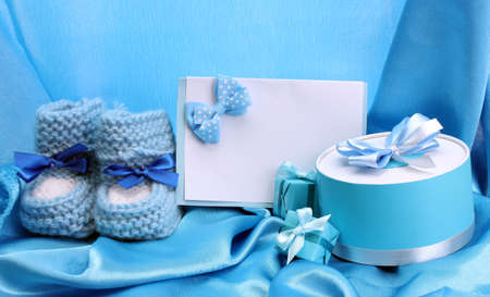 bootees: beautiful gifts, babys bootees, blank postcard and dummy on blue silk Editorial