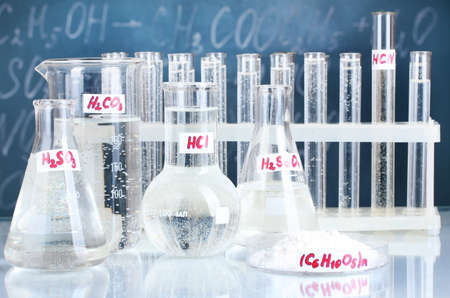Test-tubes with various acids and other chemicals on the background of the blackboard