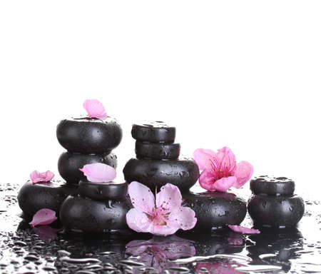 Spa stones with drops and pink sakura flowers on white background