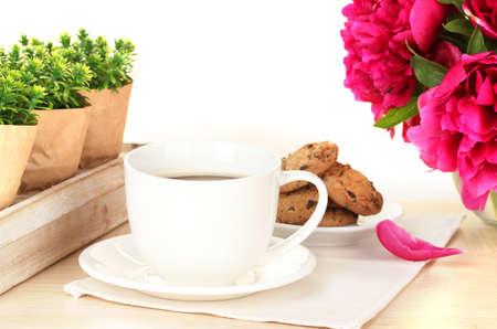 Filiżanka kawy, ciasteczek i kwiaty na stole w kawiarni Zdjęcie Seryjne - 13978577