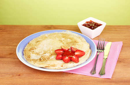 Stack of tasty pancakes on wooden table on green background Stock Photo - 13978694