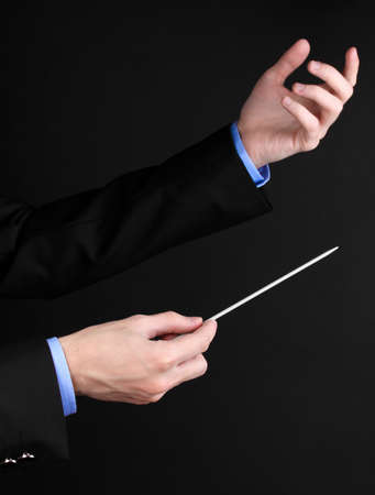 directors: Music conductor hands with baton isolated on black