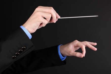 comunicacion no verbal: Música manos del conductor con bastón aislado en negro Foto de archivo